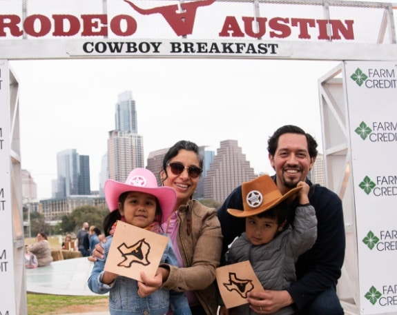 Smiling family at Rodeo Austin Cowboy Breakfast in downtown Austin